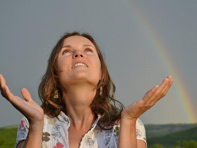 両手を広げ、空を見上げる女性