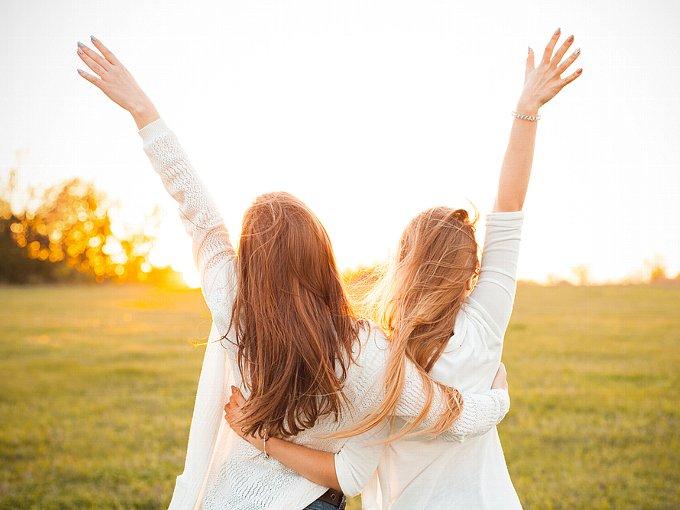 肩を組んで空に手を伸ばす女性2人