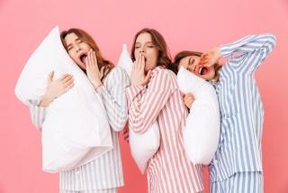 女性3人が枕を抱えてパジャマを着ている