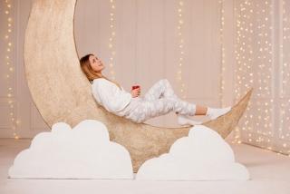 月の模型の上に女性がパジャマ姿で座っている