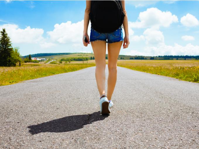 女性がスマホを握りながら散歩をしている画像