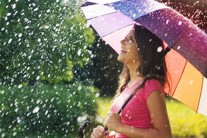 カラフルな傘を持つ笑顔で髪の長い女性