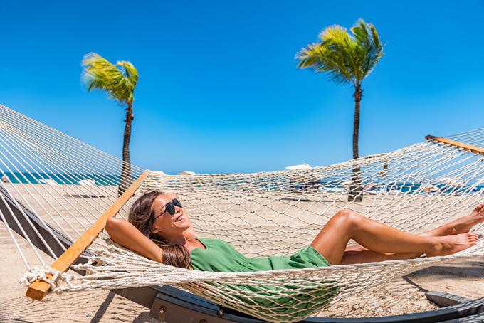 海辺のハンモックでくつろぐ女性の画像