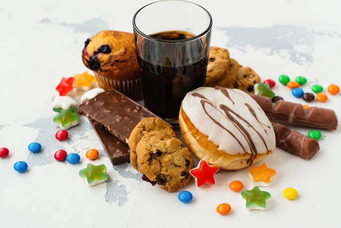 コップに入ったコーラとお菓子の画像