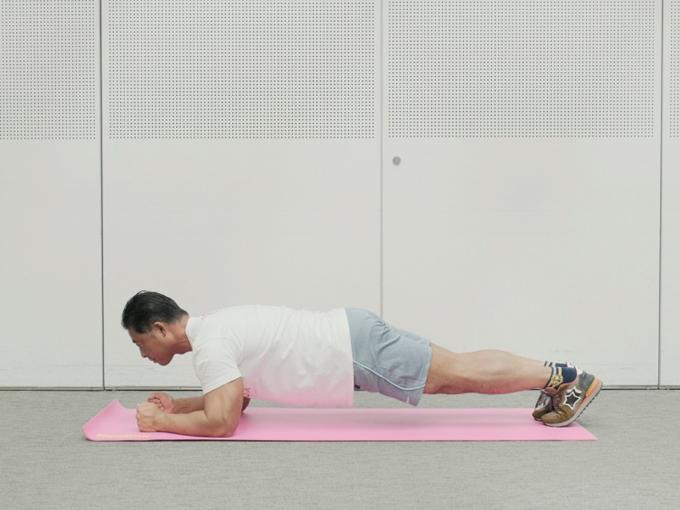 床にうつ伏せになり、ヒジとつま先で体を支える桑原先生