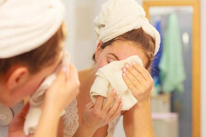 女性がタオルで顔をふいている