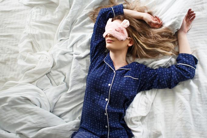 女性がベットの上で両手を上げて寝ている