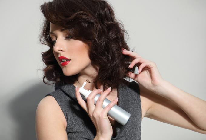スプレーを髪にかけている女性の画像