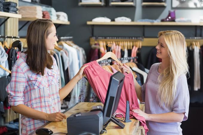 洋服を買う女性とレジに立つ店員の画像