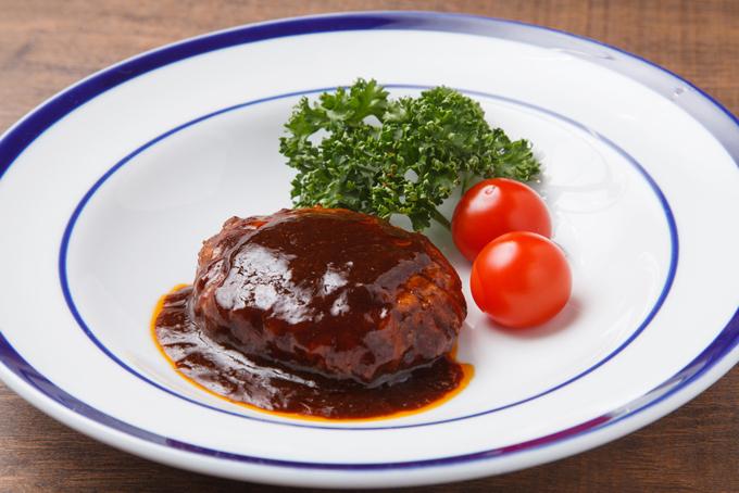 トマトとパセリが添えられたハンバーグの画像