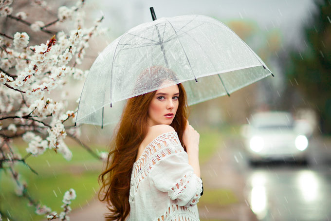 雨の中傘を持っている女性の画像