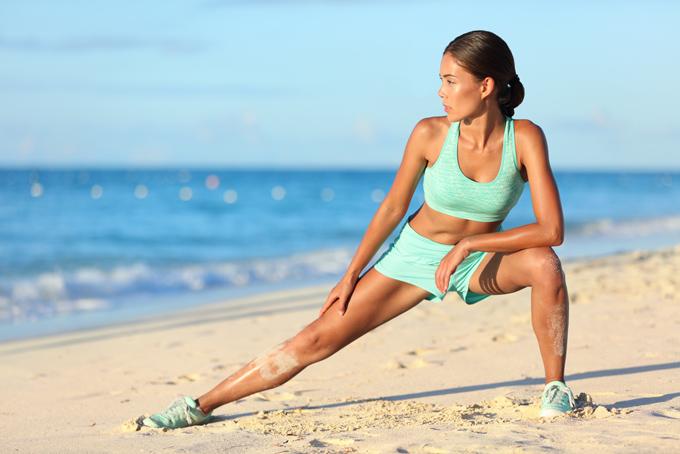 浜辺でトレーニングをしている女性の画像