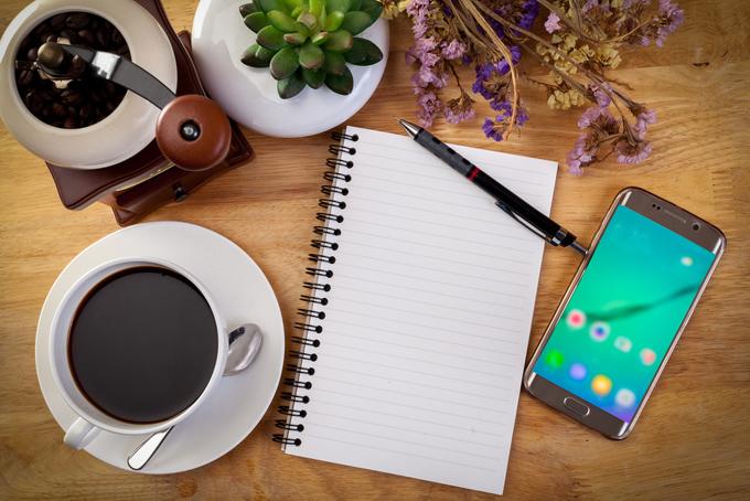 机の上にノートとペン、スマートフォン