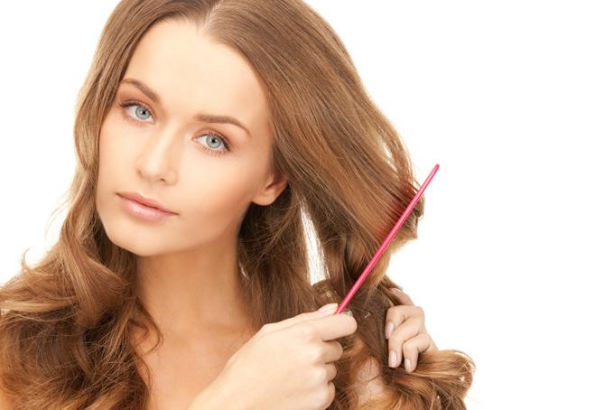 クシで髪をとかす女性の画像