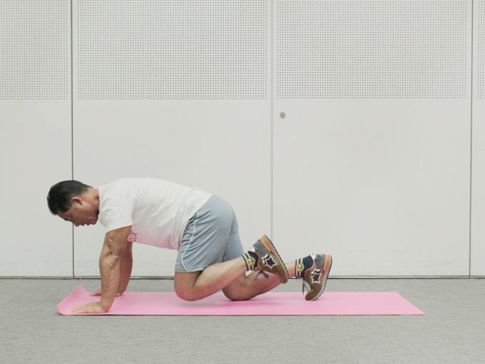 両手、両ひざを床につき、左のヒザを少しだけ床から浮かせた桑原先生