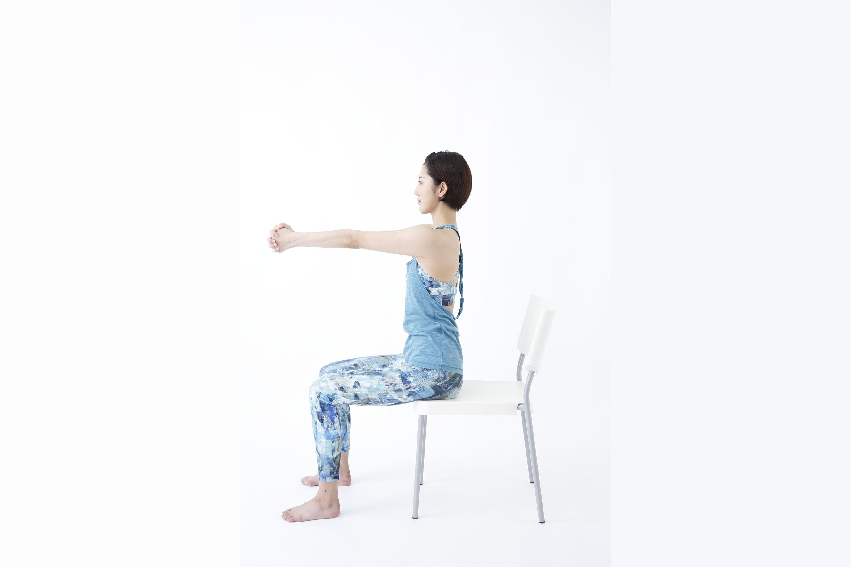 イスに座り両腕を前に伸ばす女性