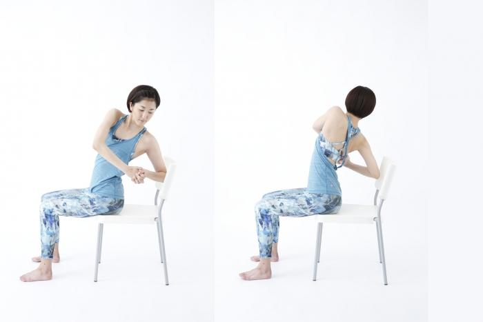 イスに座り、上体をひねる女性