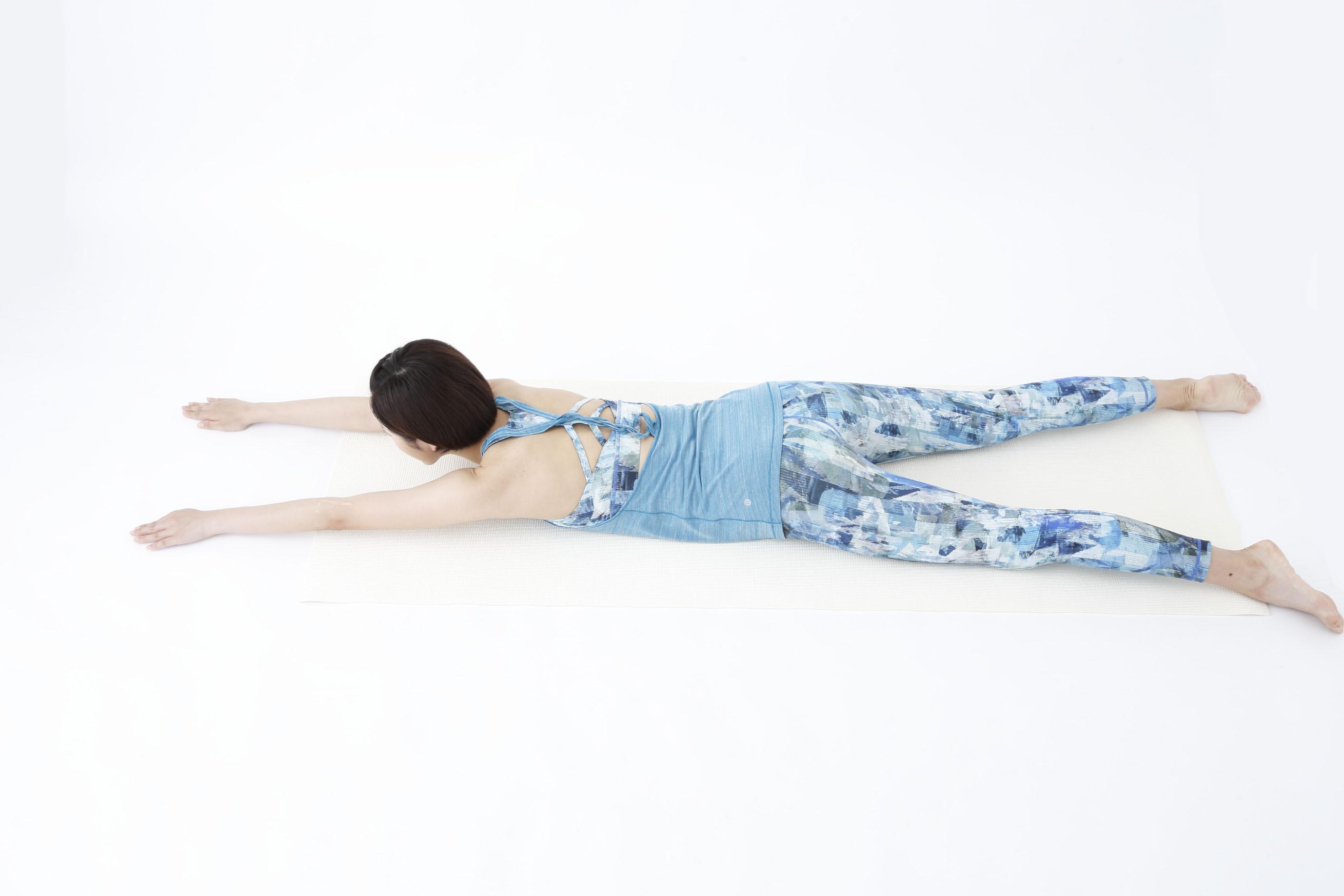 床にうつぶせになり、手脚を伸ばす女性