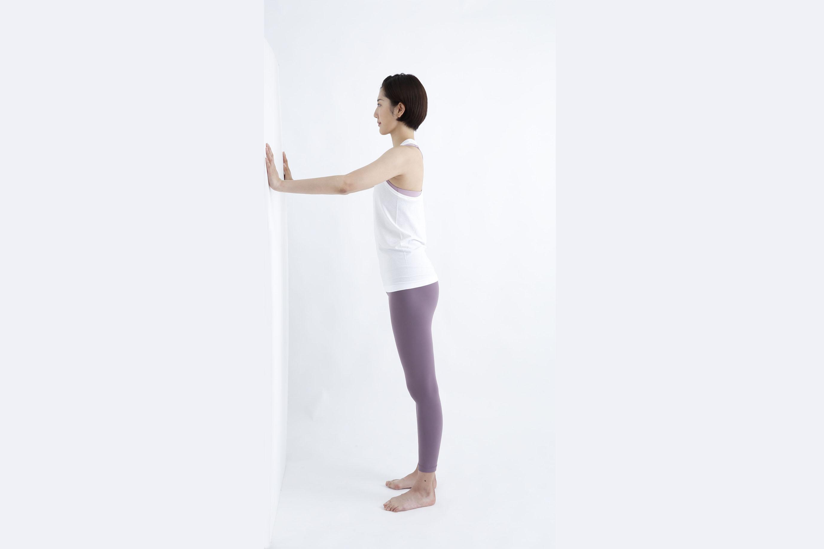 壁の前に立ち、両手を伸ばしている様子