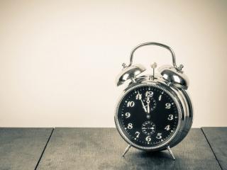 床に置かれた黒い目覚まし時計の画像