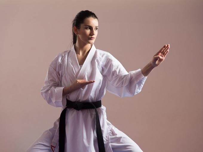 空手道着を着て拳を構えている女性の画像