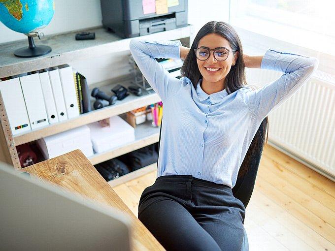 パソコンを前に、笑顔で両腕を頭のうしろで組む女性