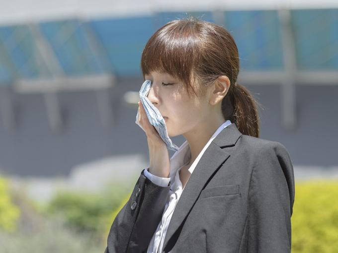 ハンカチで汗をぬぐっている女性の画像