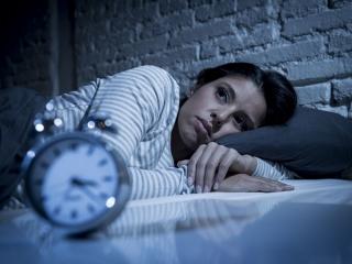ベッドに寝転んでいる女性と時計の画像