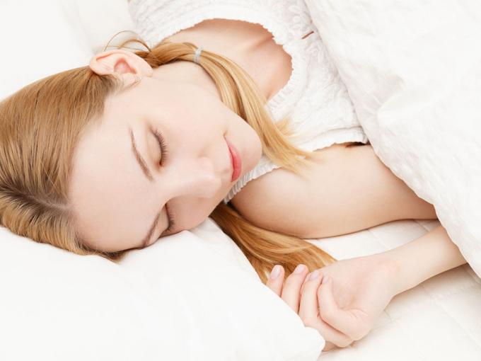 白い布団で眠っている女性の画像