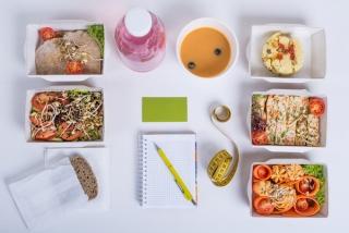 テーブルの上にお弁当やスープ、ドリンク、パン、ノートの画像