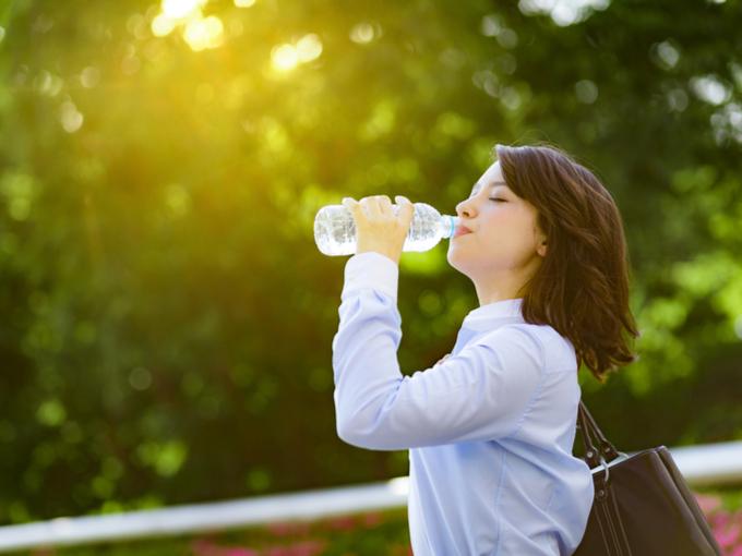 日差しの下で水を飲んでいる女性の画像