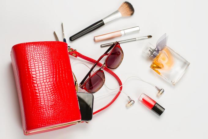 赤いバッグから飛び出ているメイク道具の画像