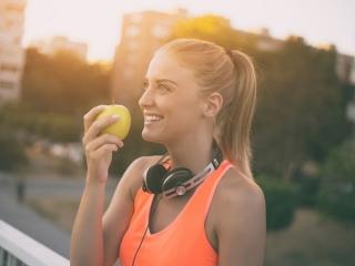 トレーニングする前にりんごを食べる女性