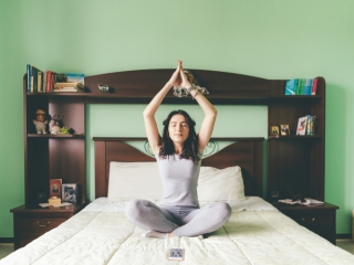 女性がベッドの上で瞑想している画像