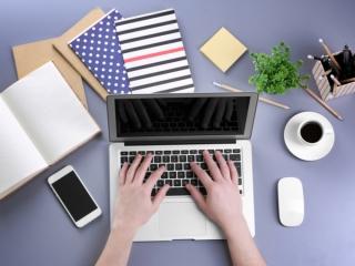 スマホを机の上に置いてPC作業をする女性
