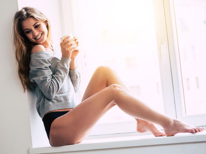 窓辺でお茶を飲む女性の画像