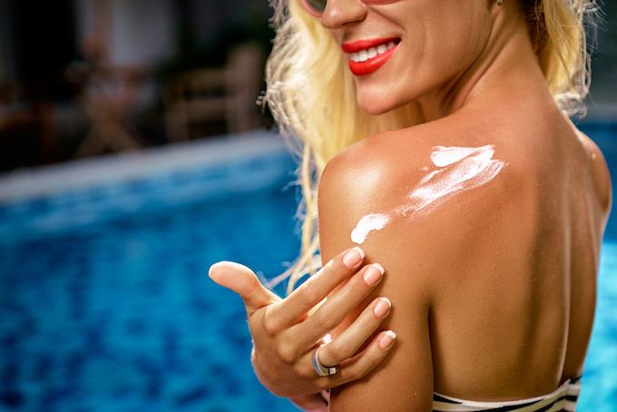 日焼け止めを塗っている女性の画像
