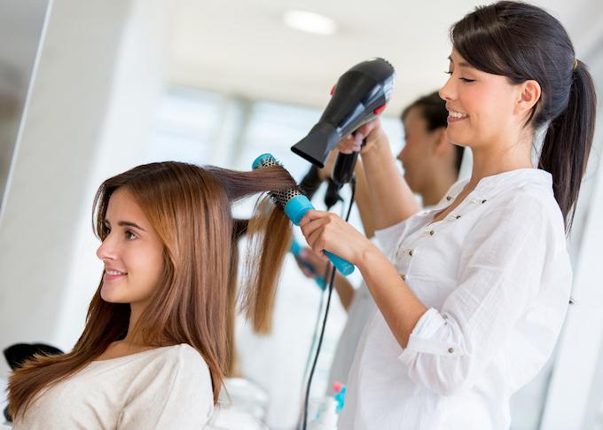 美容師に髪を乾かされている女性の画像