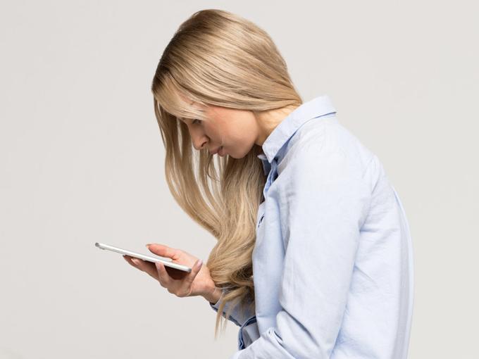 背中を丸めてスマホを見ている女性の画像