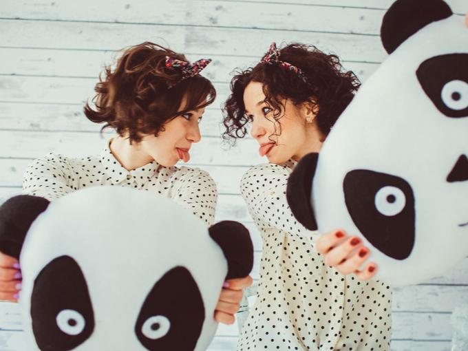 パンダのクッションを持つ双子の女性