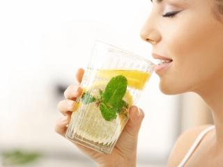 ミントとレモンのドリンクを飲む女性の画像