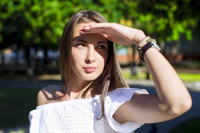 太陽光を手で遮る女性の画像