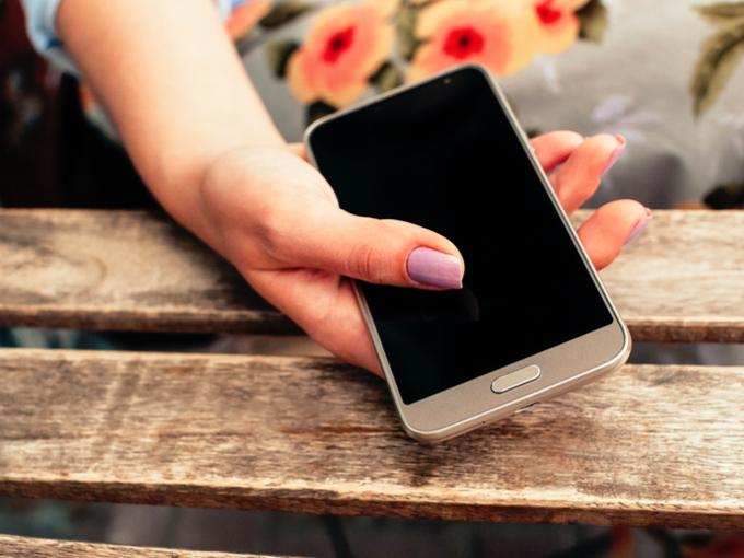スマートフォンを持つ女性の手