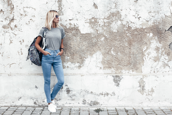 デニムを履いて壁際に立っている女性の画像