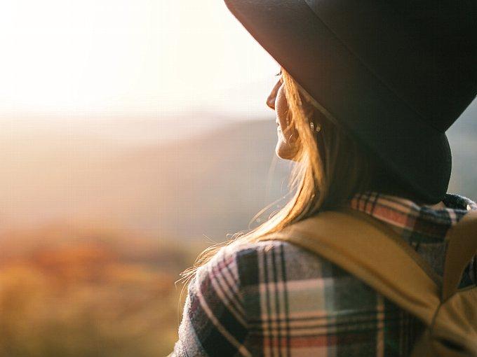 夕日の方を見つめる女性