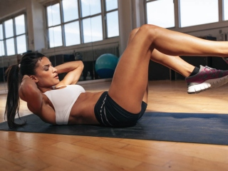 マットの上で足を上げてトレーニングしている女性の画像