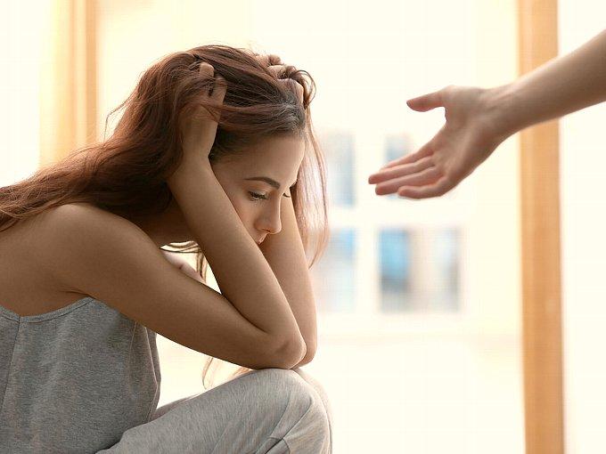 落ち込む女性に誰かが手を差し伸べている