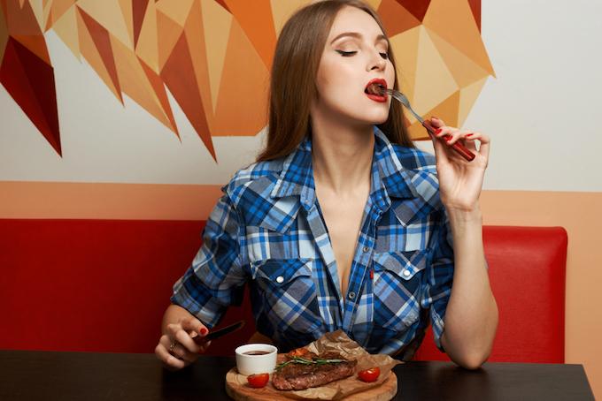肉を食べている女性の画像