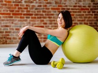 バランスボールにもたれて座っている女性の画像