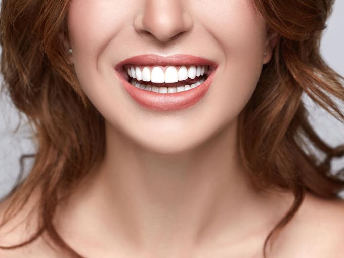 白い歯を見せて笑っている女性の画像